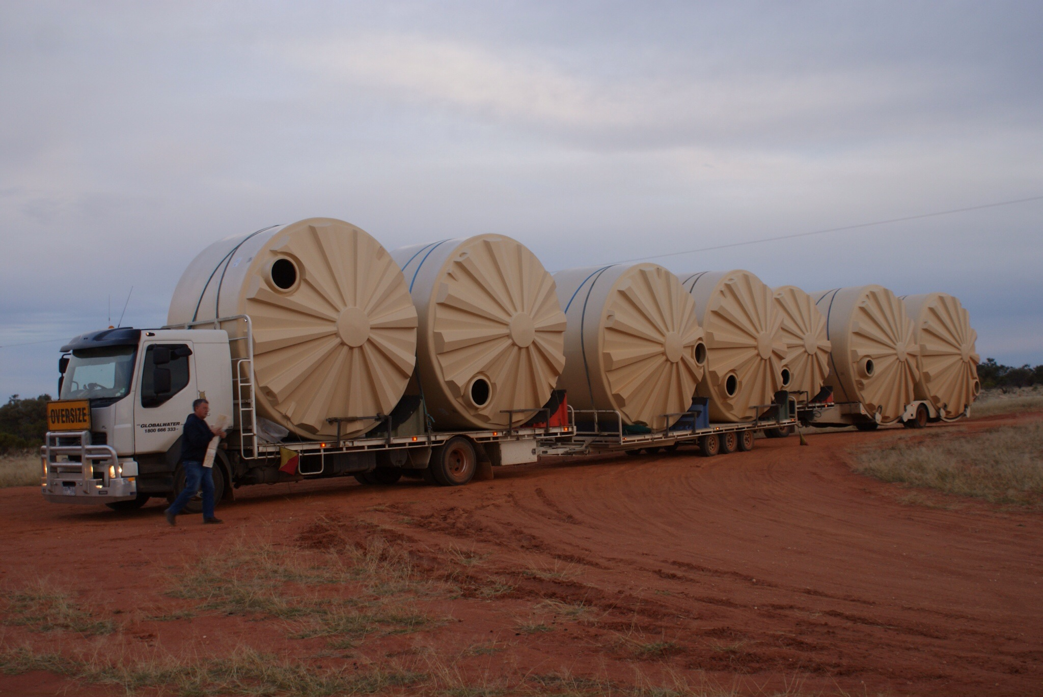 Truck Hauling Seven Large Water Tanks