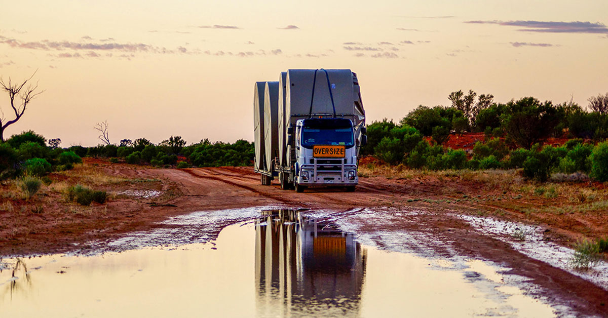 Water Tank Transport Truck Drives Over Puddle On Dirt Road