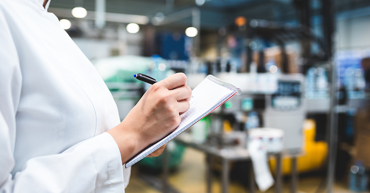 Woman In Lab Coat Writing In Notepad